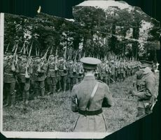 Colonial troops marching in the forest while carrying a gun, 1914.