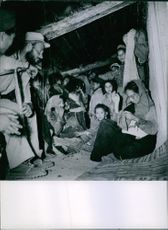 People gathered in hut, woman sewing.