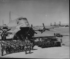 A group of soldiers and some vehicles in front of a Globemaster waiting to be loaded into the giant planet's two floors.
