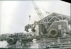 Railroad through Iran helps speed U.S. war supplies to Russian front Iranian workmen help assemble American trucks as a crane swings a chassis into position.