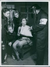 1940  A medical man in the military in Norden is talking to four Scala Girls as air raid helpers, one of them has sprained arm.