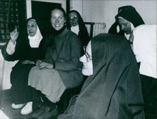 Mireille Negro with the nuns, sitting and smiling, 1973.