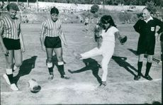 A woman kicking a soccer ball barefoot with Sacha Distel and other soccer players.