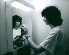 Eva Nilsson, visually impaired, facing and touching the mirror.