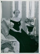 Woman sitting on couch and looking towards the camera.