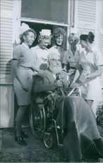 Nubar Sarkis Gulbenkian on wheelchair, surrounded by women nurses.  1970