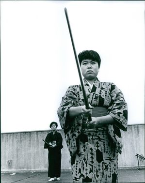 Two Japanese women wearing a kimono and holding a stick.