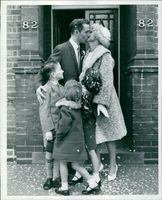 Couple kissing and children looking at them.