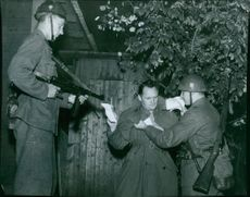"""Inductee repetition practises in action. Two soldiers arrest a """"sabotar"""" found with anti military propaganda."""