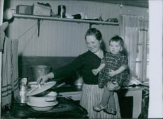 Maria Olep carrying her son while making a food during Sweden in World War II, 1944.
