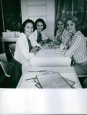 A photo of  Celebrity twins Alice and Ellen Kessler sitting in the table facing another twins celebrity.
