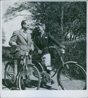 Einar Oscar Beyron and Brita Hertzberg with cycles while smiling together.