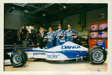 sportsmen standing with Yamaha Corporation's formula one car.