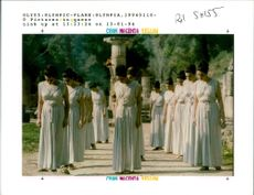 Greek actresses dressed as priestresses salute the sacred olive tree at ancient.