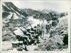 These sons of Nippon, fully armed and carrying their country's flag, are march over mountainous terrain in single file.  Date: 12/08/1935