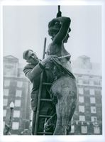 Man taking measurement of a statue with a measuring equipment.