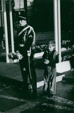 A royal guard standing beside a young boy.