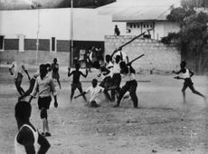 Boys in school hitting another boy brutally with the wooden stick. 1960