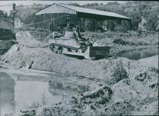 A US tankdozer on its way to a Holland river rides over a dirt fill it made across a canal in northern Holland to aid the Allied advance.