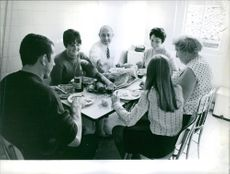 Lucien Neuwirth eating with a group of people, 1967.