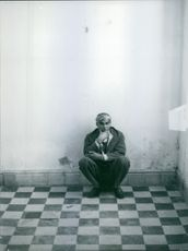 Man sitting while leaning on  the wall.