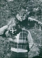 An owl perching on woman's shoulder.