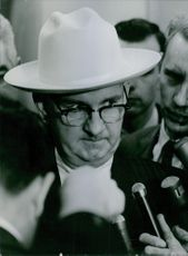 A man wearing a hat being interviewed by the press people.