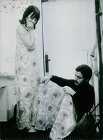 Paco Rabanne attending to his model.