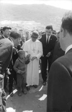 Pope Paul VI offering kid something.