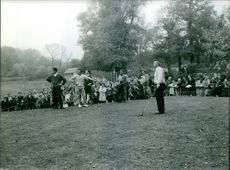 People playing golf with spectators watching them on their tournament.