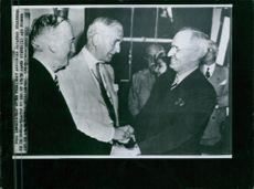 Immediately after president announced japanese surrender he is congratulated by Sec. of State James Byrnes(L) and former Sec. of State Cordell Hull (center).