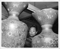 Eartha Kitt looks unimpressed by two immense vases.