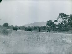 Soldiers marching along the grass field.