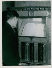 Man reading Civilian War dead list in westminster abbey place in a shrine.