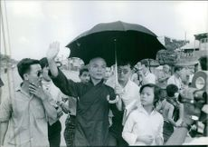 Monk walking in Saigon with people and waving hand.