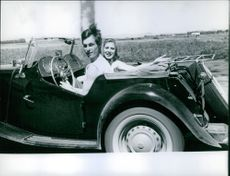 Suzy Parker riding a car with a man looking towards the camera and smiling.