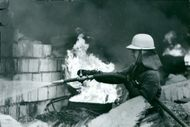 A firefighter fighting fire in the ruins area.