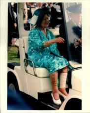 Queen Elizabeth takes a golf car on her way to an event.