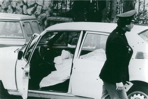 Car with ballhole and a covered body of a bodyguard inside after Aldo Moro's kidnapping of the Red Brigades