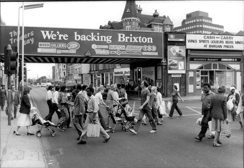 A black and white image of people walking across a street in Brixton, a suburb of London.