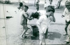 A child crying, other children washing their face in streets of Saigon. 1964.