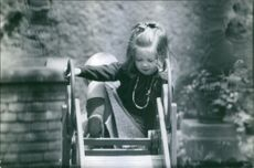A photo of a little Princess Princess of Greece and Denmark climbing a  ladder to slide.