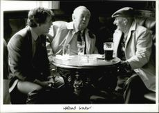 Harold Wilson gathered and talking with the men while drinking.