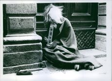 An old poor man sitting alone in street and playing musical instrument. 1970