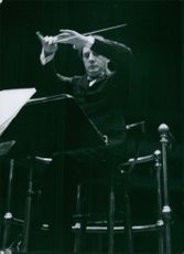 Sir John Barbirolli conducts.  He sits down, but the baton rests.