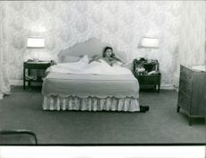 Sacha Distel is relaxing in the bed while having a conversation on the phone.