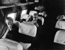 Vincent Auriol sitting on plane reading newspaper, with wife.
