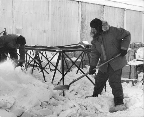 Workers shovel the snow outside the Galbraith building in Alaska.