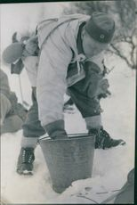 A man picking up things from snow ground. 1940