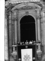 Pope Paul VI standing with other people.